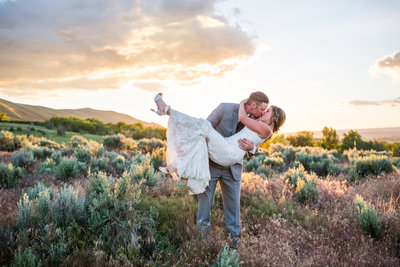 Bride and groom in passionate kiss at sunset in field in New Mexico
