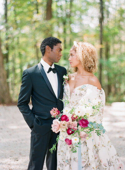 Bride and groom embrace in tuxedo and beautiful floral wedding gown