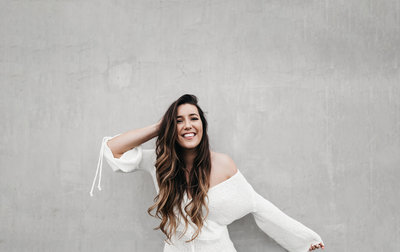 athena-grace-white-dress-fun-concrete-wall-laugh