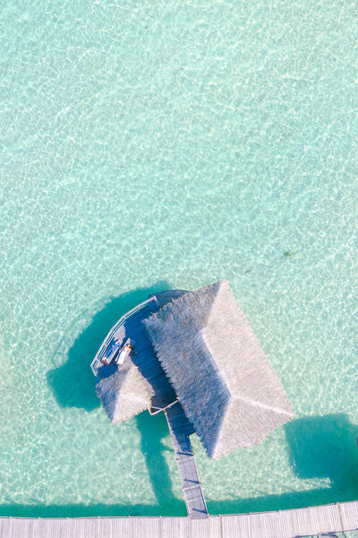 Aerial view on the overwater bungalow at le Tahaa island resort with the bride and the groom