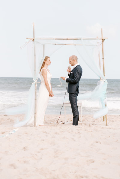 groom recites wedding vows to his bride on the beach