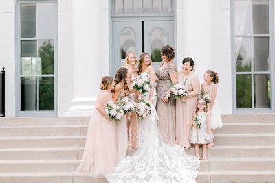 bridesmaids with bride on the stairs at canitgny park looking at each other