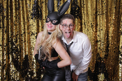 couple posing front of a gold and black backdrop having bunny ears