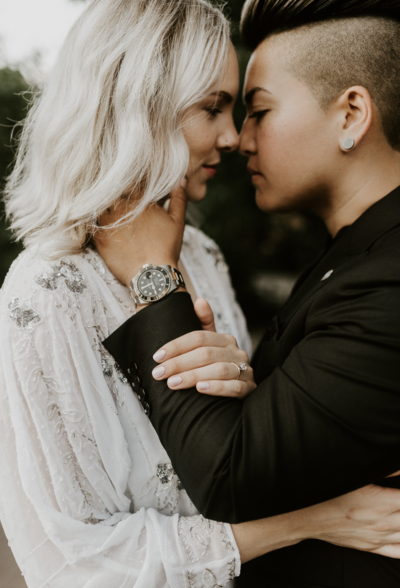 partners hold each other's faces with their engagement ring and engagement watch in view in dumbo brooklyn