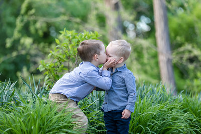 two little boy brothers kissing  at the park in la crosse