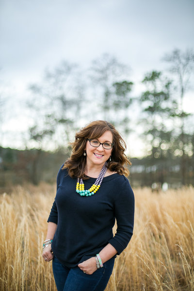 Photographer, Corry Frazier, smiles for photo in navy sweater and colorful necklace in golden field