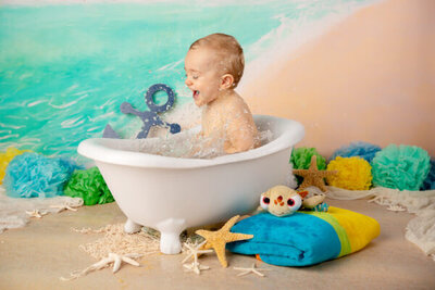 Baby boy splashes in a tub in a Myrtle Beach themed first birthday photoshoot