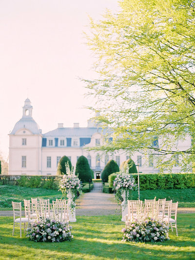 Romantic wedding ceremony set up in dusty purple and white in front of Kronovalls vinslott in sweden