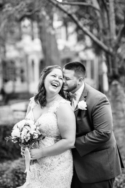 black and white photo of bride laughing and groom  behind her with his nose at her temple