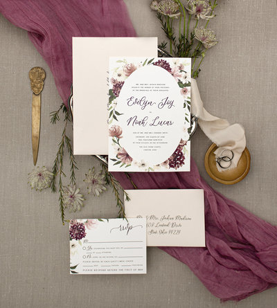 Hydrangeas, Peonies, Ranunculus and Anemone flowers are beautifully painted in watercolor around the invitation. Leafs and blooms peak from behind the oval shape creating depth, beauty and interest.  4 Piece Suite