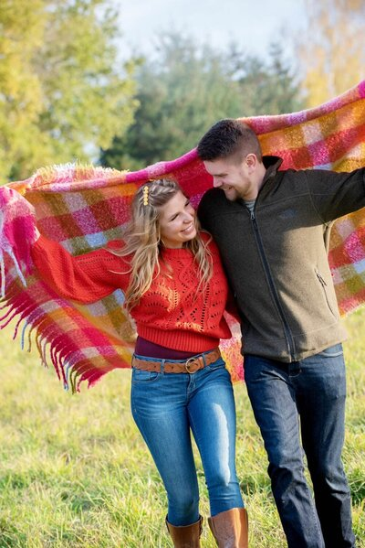 a couple in bright colors run holding a vibrant blanket over their heads