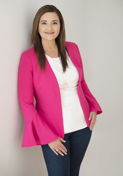 headhot of realtor woman  shoulder length hair , wearing pink jacket and  standing with hands in pocket of denim pants . powerful and  confident  entrepreneur