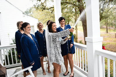 Bride and bridesmaids celebrate with champagne at  The Venue at Southern Oaks, Mississippi  Wedding