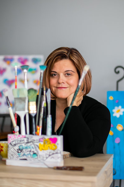 Artist in black sweater poses for photo behind her paint brushes in her studio