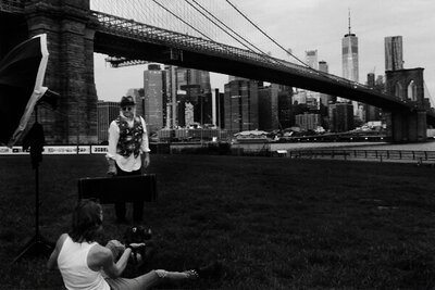 black and white bts image Mark Maryanovich sitting on ground photographing musician Robert Allen standing by Brooklyn Bridge flash directed at him