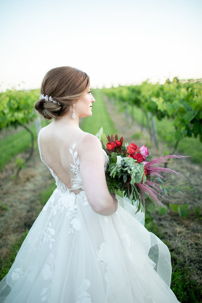 Bride in wedding gown with bouquet looks out over the vineyards at Providence Vineyard in Hebron, IL