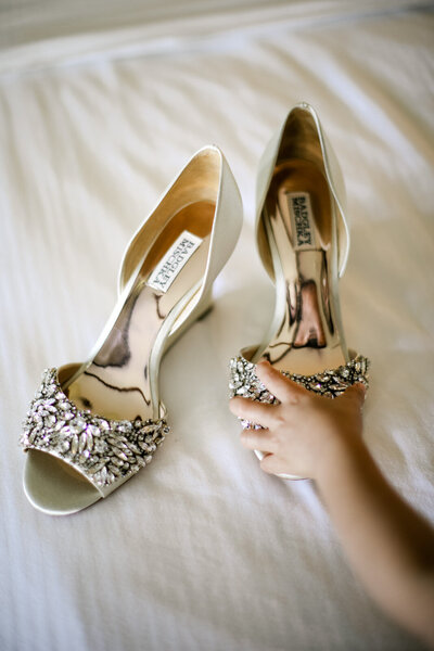 A little girl grabbing jeweled wedding shoes