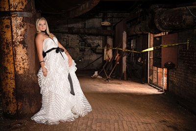 High school senior girl in white tiered dress with black sash leaning against a metal pole among rusted steel at Carrie Furnace in Pittsburgh, PA