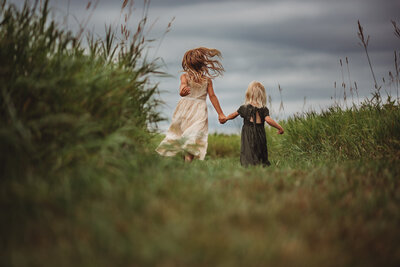 Two young girls holding hands and running away in a filed