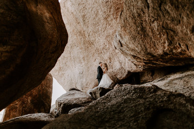 Couple standing in boulders