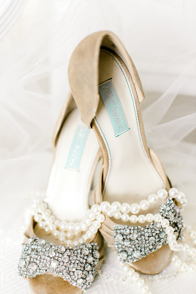 Pearl necklace draped over sparkly Betsey Johnson bridal heels and veil