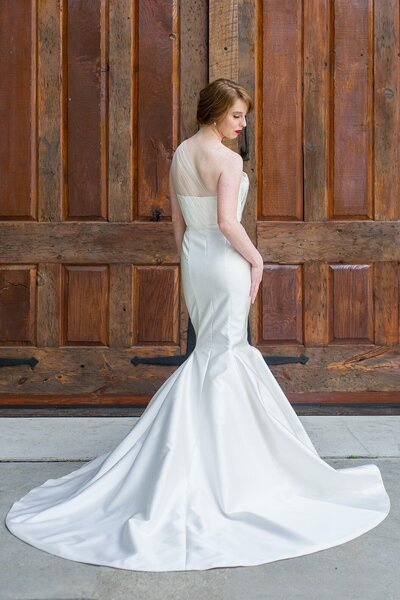 Back view of the Natalia wedding dress with its asymmetrical bodice and mikado skirt from the Classics bridal collection