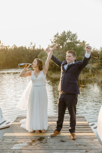 Bride and groom cheer and drink champagne at the end of a dock