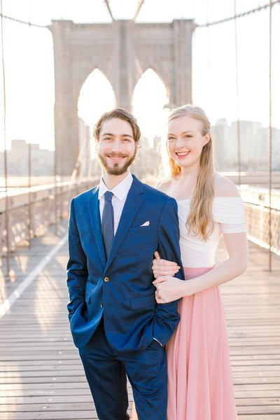 Man and woman smiling at camera at the Brooklyn Bridge in New York City
