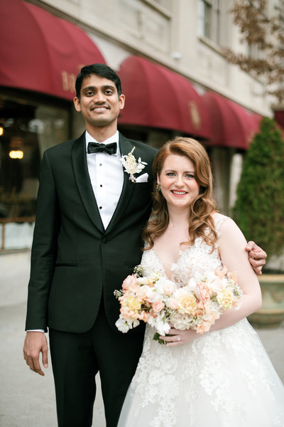 bride and indian groom pose in front of the brown hotel in louisville with a all dried floral boutonniere and a pastel colored bridal bouquet by roots floral design