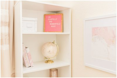 white bookshelf with pink letterboard and pink globe
