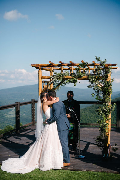 couple on top of hunter mountain having their first kiss as husband and wife