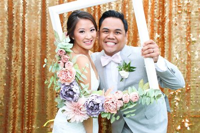 lovely couple posing front of a gold backdrop holding a floral frame