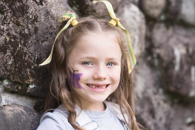 young girl with yellow ribbons in her hair and a purple butterfly on her cheek
