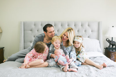 family of 6 on bed in pajamas with newborn