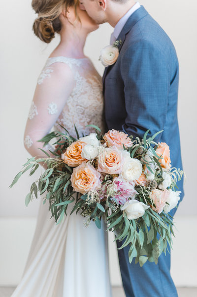 a bride and groom with a bouquet of ivory, pink and peach at Red Rock Casino Resort and Spa in Las Vegas