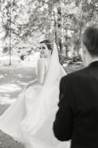 black and white image of bride and groom walking away from the camera as the bride is looking over her shoulder while her groom holds her dress