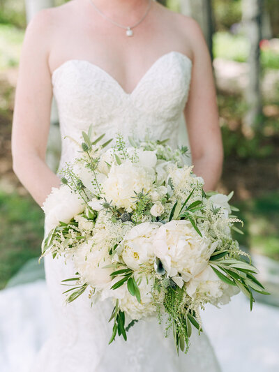 Close up of a bride holding a large white and green bouquet