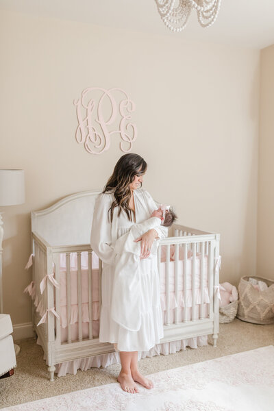 newborn in crib under a monogram