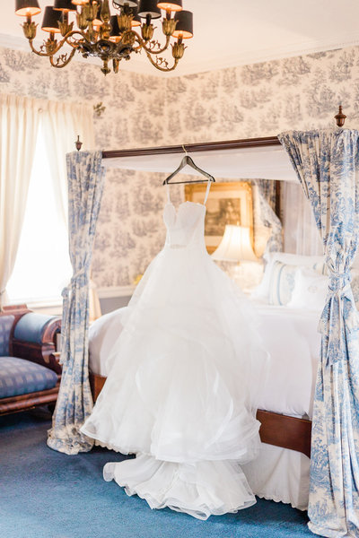 Wedding Dress hanging on a hanger above a beautiful country style bed