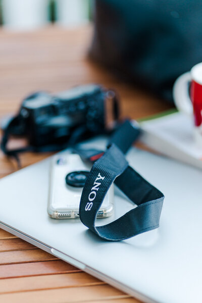 sony camera strap and iphone lying on a white desk