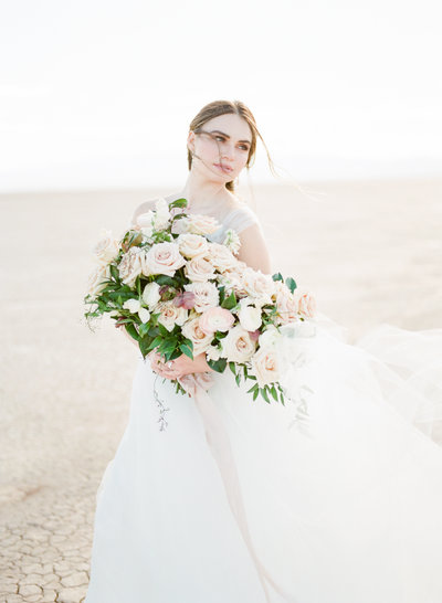 Bride stands windswept while holding bouquet in wedding dress in the desert