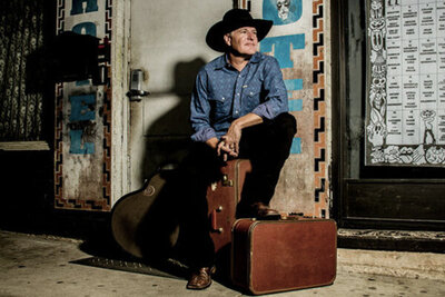 Country musician portrait Darrell Goldman sitting on suitcase one foot resting on another piece of luggage guitar resting on wall behind him