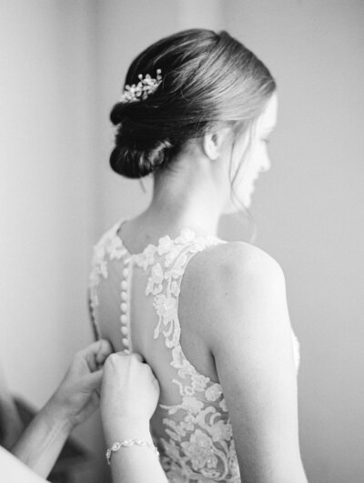 black and white image of bride getting her dress on