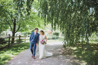 Bride and groom share a happy moment while carrying brightly colored bouquet down tree lined path