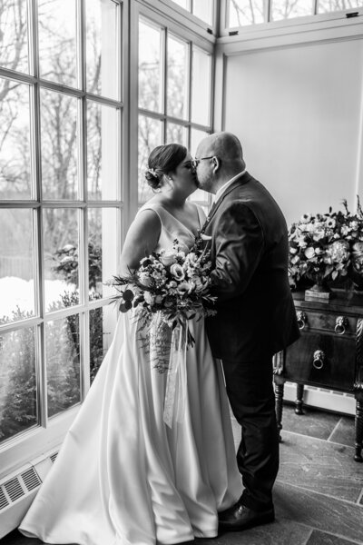 Bride and groom kissing in front of window black and white