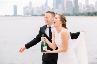 Bride and groom pop champagne Lake Michgan