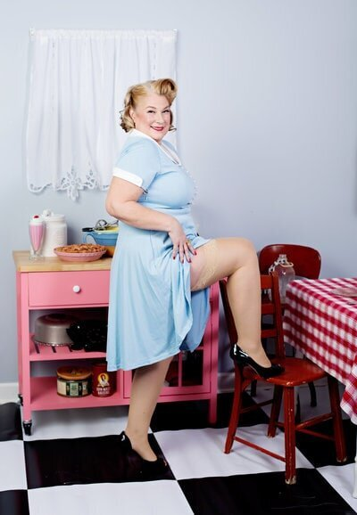 Blonde woman in light blue pinup dress, posing in the pinup kitchen at boudoir and pinup by Janet Lynn