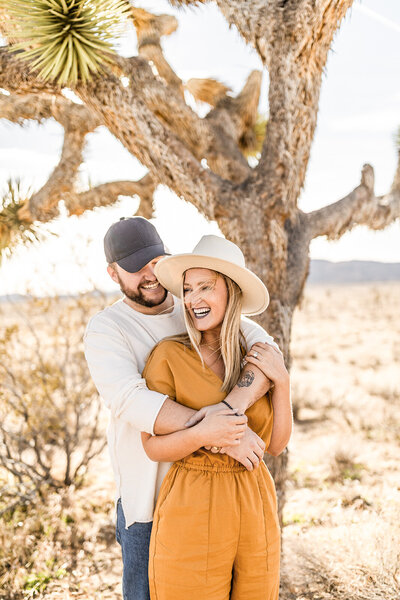 couple hugging in front of joshua tree