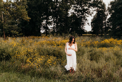 Pregnant woman standing in yellow flowers field