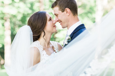 Young couple with brown hair smiling at each other in wedding attire and veil draped around them